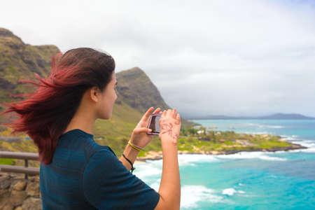Biracial Asian Caucasian teen girl taking photo of beautiful blue Hawaiian ocean and coast from above at Makapu'u Lookout looking over Makapu'u Beach Park on windy day