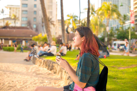 Biracial teen girl sitting at Waikiki beach near sunset eating spam musubi with crowd of tourists blurred in background