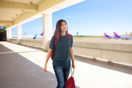 Teen girl carrying red backpack and bag walking through outdoor airport terminal with blurred airplanes in background on sunny day