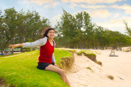 Biracial teen girl sitting along grassy dunes on sunny Hawaiian beach by the ocean, arms raised enjoying the wind