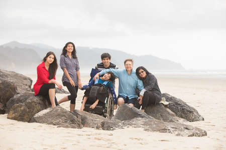 Interracial family of six sitting together on beach with special needs child in wheelchair