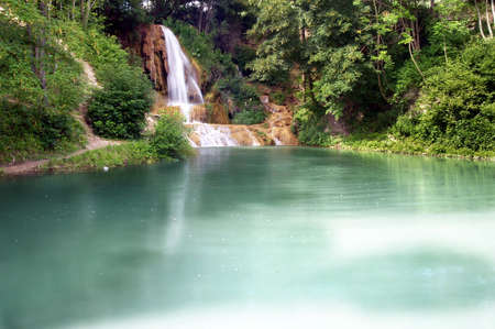 A view of a lake and waterfall in summer. photo