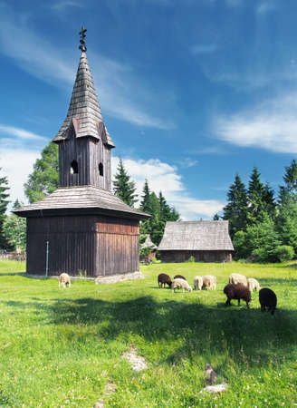 Rare wooden bell tower with sheep nearby during summer photo