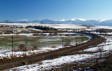 Railroad or train tracks passing through open prairie with mountains in the background photo