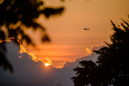hostile: An airplane flies through during the sunset Stock Photo