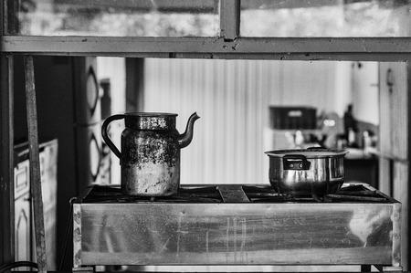 cocina vieja: Antigua cocina con un hervidor de agua y una olla sobre una estufa de vista a través de una ventana
