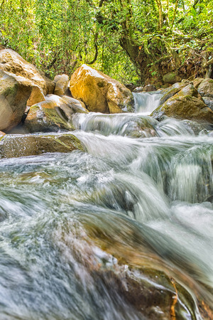 current: River current flowing through the rocks