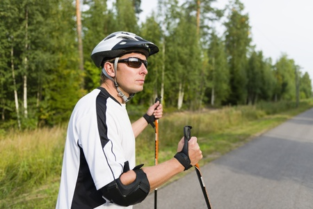 blading: Man rollerskating with the rods. Stock Photo