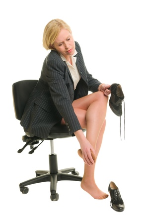 Officewoman rub her legs, white isolated background.