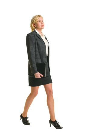 suit skirt: Businesswoman walking forward and holding her organizer, white isolated background. Stock Photo