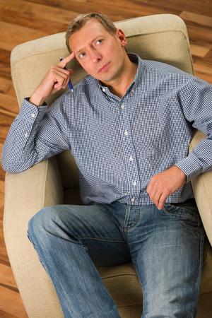 introspective: Man sitting on the armchair and thinking something.