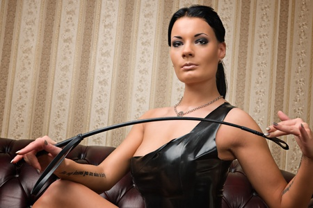 A young brunette lady mistress and leather couch on background  Stock Photo
