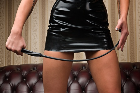 A young lady mistress with a whip, leather couch on background Stock Photo - 12498632
