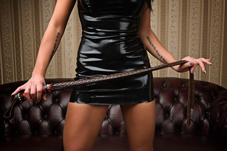 A young lady mistress with a whip, leather couch on background