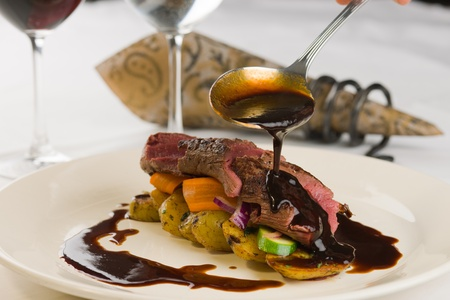 Roasted reindeer sirloin and place setting, red wine sauce is poured