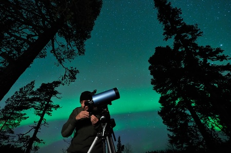 One night man watching northern sky, aurora behind.