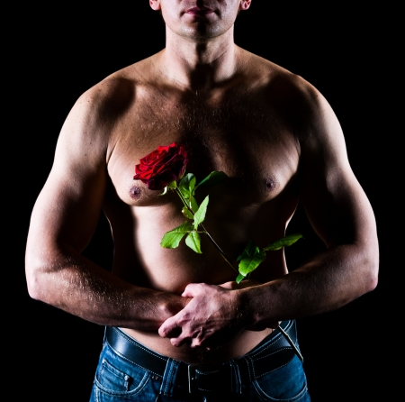 Handsome caucasian man to keep a rose front of chest photo