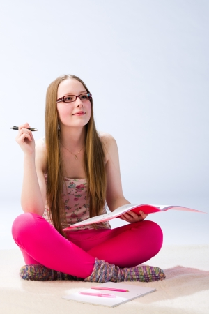 A young beautiful girl student pondering in the middle of study