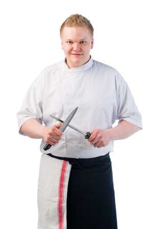 Young cook sharpening his knife, white isolated background photo