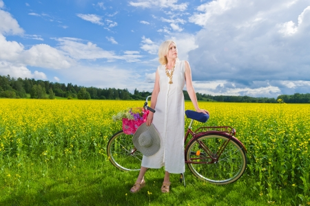Woman with bicycle standing in front of the field, sunny day photo