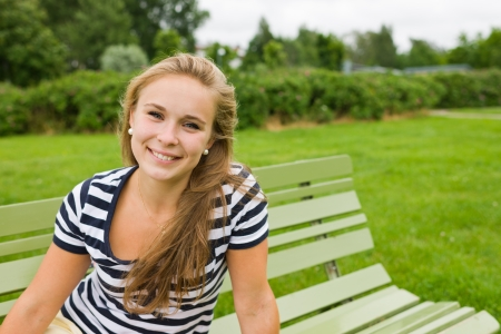 Young smiling girl sitting on the park chair and focus on her eyes