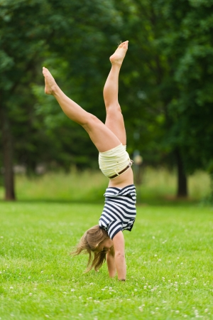 headstand: Young girl doing headstand at the park with narrow depth of field