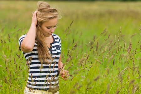 meadowland: Young beauty girl on the meadow with very narrow depth of field and focus on the hay on the hand Stock Photo