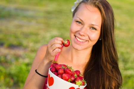Beautiful girl pick up a strawberry from a bowl, focus on the eyes, landscape image