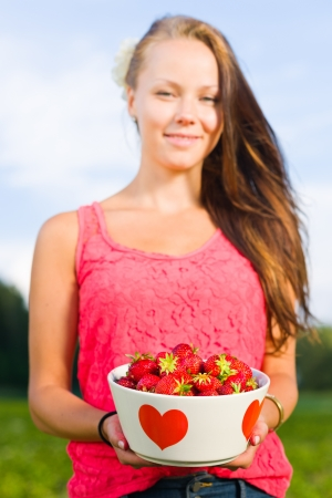 Beautiful girl holding a bowl of fresh strawberries, focus on the eyes photo