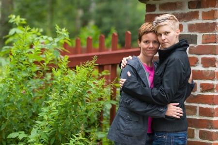 homosexuales: Dos ni�as abrazos delante de la valla y se ven hacia el horizonte de formato de c�mara,