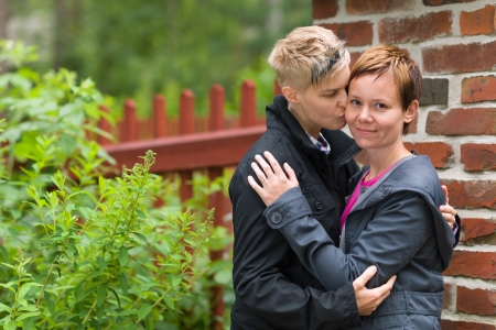 lesbian couple: Two girls hugging together front of fence, horizon format