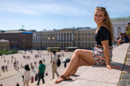Beautiful girl sits on the stairs of Helsinki Cathedral, on the background the Senate square, horizon format