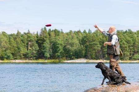 dog rock: Man train his retriever by throwing a dummy