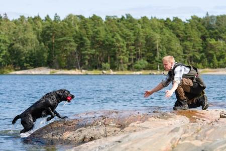 The Labrador retriever fetch a dummy for its owner Standard-Bild