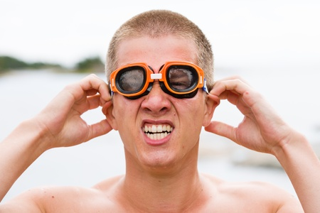 clowning: Clowning young swimmer wears swimming goggles on