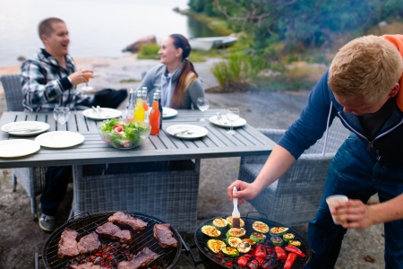 Meat and vegetables in grill, young couple laughing on background