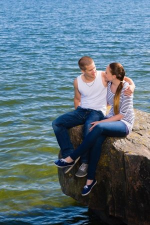 scandinavian people: Young lovers looking and hugging each other on big rock Stock Photo