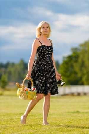 Woman goes to the picnic, barefoot, she looks toward camera photo