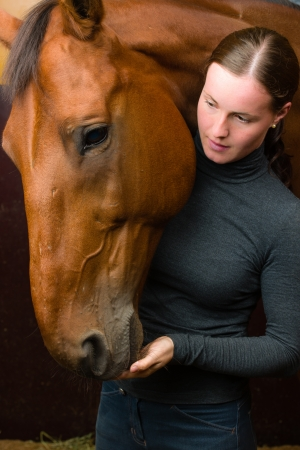 half blooded: Woman give a tidbit to horse, vertical format