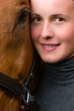 half blooded: Woman and horse together, woman looks toward camera, vertical format
