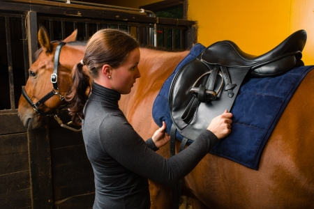 headcollar: Woman saddle a horse in the stall