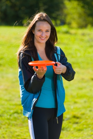 disc golf: Beautiful woman poses with a disc, vertical format