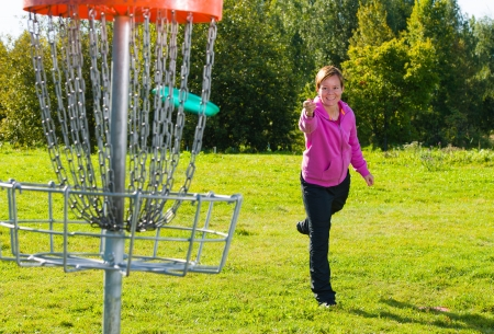 Woman throwing a disc to the disc basket photo