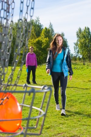 disc golf: Disc inside of the basket, players on the background, focus on the closest player