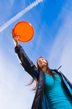 Woman holds a orange disc and attend to throw, blue sky on background