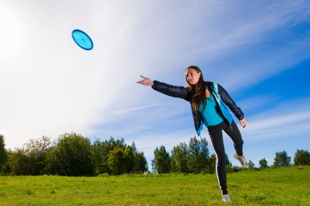 Woman throws a blue disc on the lawn Stock Photo