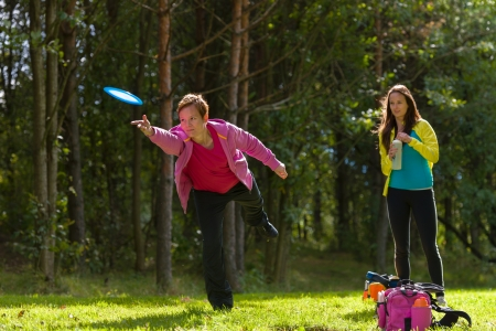 disc golf: Woman throws a disc, friend waiting on background Stock Photo