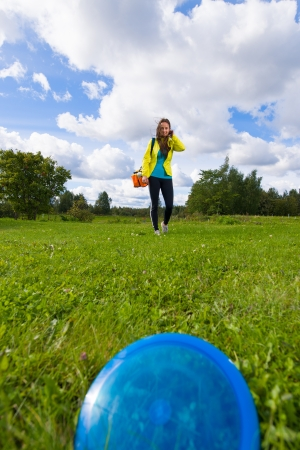 disc golf: Blue disc on the lawn, on background woman walks over disc Stock Photo