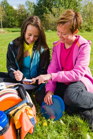 disc golf: Women checks accounting during the pause, vertical format Stock Photo