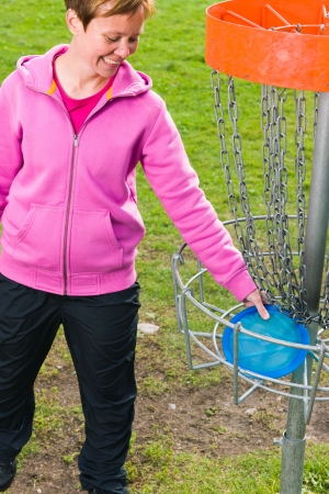 disc golf: Woman pick up a disc out the basket, vertical format Stock Photo